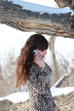 Meisje dichtbij de de wintereik, die op celtelefoon spreekt stock fotografie