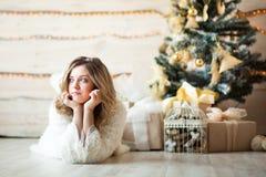 Meisje dichtbij de verfraaide Kerstboom in mooi licht binnenland Stock Foto's