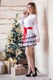 Meisje dichtbij de verfraaide Kerstboom in mooi licht binnenland Royalty-vrije Stock Afbeelding