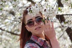 Meisje dichtbij een bloeiende boom in de lente stock foto
