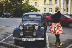 Meisje dichtbij een retro auto Stock Fotografie