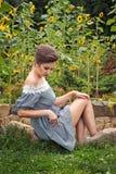 Meisje dichtbij zonnebloemen in een korte kleding 23 Stock Foto