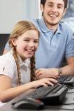 Meisje die één tot één hulp van leraar ontvangen stock afbeelding