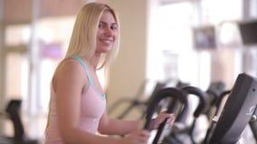 Meisje die aan camera tijdens training op orbitrek glimlachen stock footage