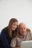 Meisje die aan haar grootvader met de computer helpen Stock Afbeelding