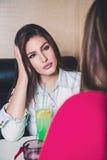 Meisje die aan haar vriend en het drinken cocktail spreken Stock Fotografie