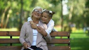 Meisje die aan het boek van de grootmoederlezing in park lopen, en haar koesteren kussen stock videobeelden