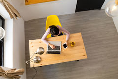 Meisje die aan laptop en cellphone thuis werken Stock Foto