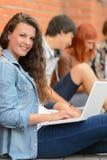 Meisje die aan laptop vrienden op achtergrond werken Stock Foto