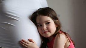 Meisje die aan moeders zwangere buik luisteren stock video