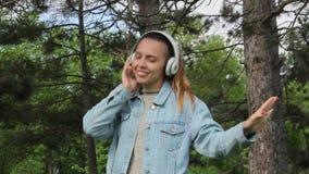 Meisje die aan muziek in hoofdtelefoons luisteren openlucht stock footage