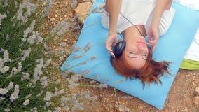 Meisje die aan muziek met hoofdtelefoons in de zomer luisteren stock videobeelden