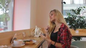 Meisje die aan muziek in moderne koffie luisteren Het straatverkeer is bij de vensterbezinning stock video