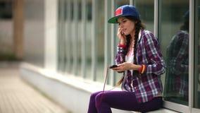 Meisje die aan muziek op een mobiele telefoon luisteren