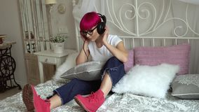Meisje die aan muziek op hoofdtelefoons op het bed luisteren stock footage