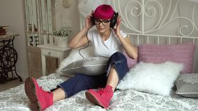 Meisje die aan muziek op hoofdtelefoons op het bed luisteren stock videobeelden