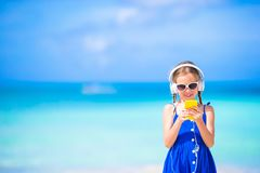 Meisje die aan muziek op hoofdtelefoons op het strand luisteren Stock Foto