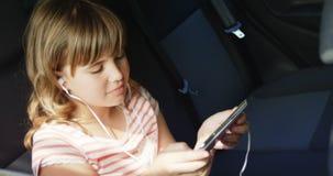 Meisje die aan Muziek op Mobiele Telefoon luisteren stock footage
