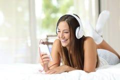 Meisje die aan muziek van een smartphone thuis luisteren Stock Foto