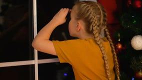 Meisje die aan venster, wachtende Santa Claus, geloof in Kerstmismirakel kijken, kinderjaren stock videobeelden