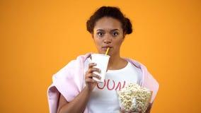 Meisje die aandachtig op film letten en frisdrank, invloed drinken van televisie stock afbeelding