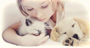 Meisje die affectionately katje en Puppy koesteren stock fotografie