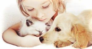 Meisje die affectionately katje en Puppy koesteren stock afbeelding