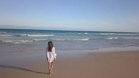 Meisje die alleen op het strand lopen stock video