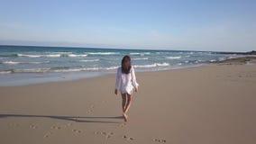 Meisje die alleen op het strand lopen stock footage