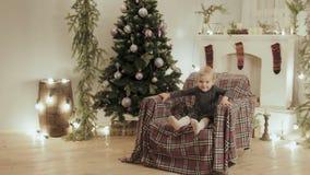 Meisje die als voorzitter voor het nieuwe jaar op de achtergrond van Kerstmisdecoratie springen stock videobeelden