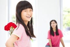 Meisje die anjerbloemen geven aan moeder stock afbeeldingen