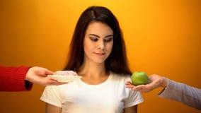 Meisje die appel in plaats van doughnut, natuurlijke suiker en vitamine versus banketbakkerij kiezen stock fotografie