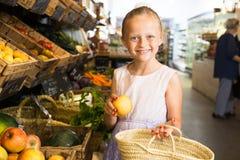 Meisje die appelen in plantaardige winkel kiezen op het uithangbord inscrip royalty-vrije stock afbeelding