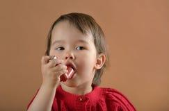 Meisje die astmatisch geneeskundeinhaleertoestel ademen royalty-vrije stock afbeeldingen