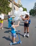 Meisje die ballons geven aan jongen Stock Afbeelding