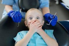Meisje die bang van controle bij tandartsen zijn stock afbeelding