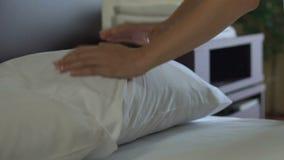 Meisje die bed maken en hoofdkussens in vijfsterrenhotel, de onberispelijke dienst aanpassen stock videobeelden