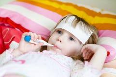 Meisje die in bed met een thermometer liggen royalty-vrije stock afbeeldingen