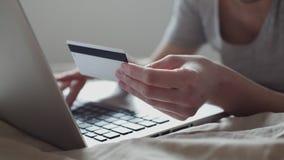 Meisje die in bed online met creditcard winkelen stock footage