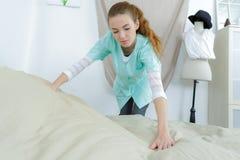 Meisje die bed in verpleeghuis maken stock afbeeldingen