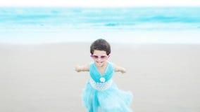Meisje die & bij blauw strand lopen spelen Stock Afbeeldingen