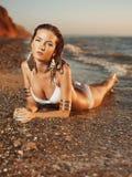 Meisje die bij de overzeese kust liggen Royalty-vrije Stock Afbeeldingen