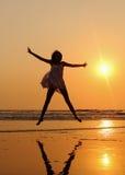 Meisje die bij het strand springen royalty-vrije stock afbeeldingen