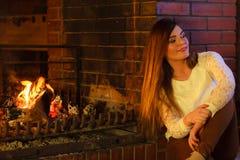 Meisje die bij open haard opwarmen stock afbeeldingen