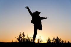 Meisje die bij zonsondergang springen Stock Afbeeldingen
