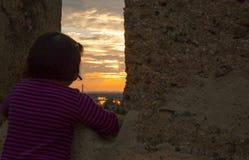 Meisje die bij zonsondergang van de Middenleeftijdsmuur staren van Badajoz, Spanje Royalty-vrije Stock Fotografie