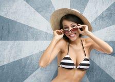 Meisje die bikini, hoed en zonnebril op gestreepte achtergrond dragen royalty-vrije stock fotografie