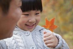 Meisje die blad met haar vader bekijken, close-up, de herfst Royalty-vrije Stock Afbeeldingen