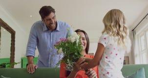 Meisje die bloemboeket geven aan haar moeder in woonkamer thuis 4k stock video