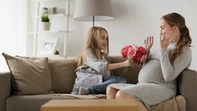 Meisje die bloemen thuis geven aan haar zwangere moeder stock footage